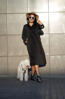 Spring collection. happy pretty brunette girl wearing stylish black dress and fashionable sunglasses posing with cute dog. model in trendy outfit posing on grey wall background. outdoor portrait.
