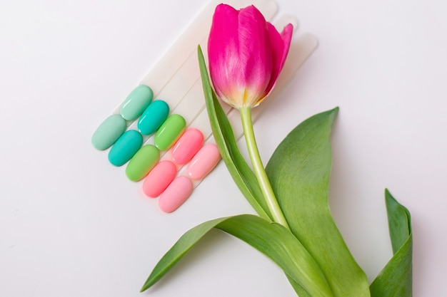 Spring color palettes of nail gel polish for manicure and pedicure with a tulip on