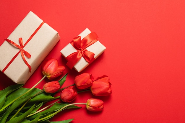 Spring composition. bouquet of red tulips and gift box on red background.