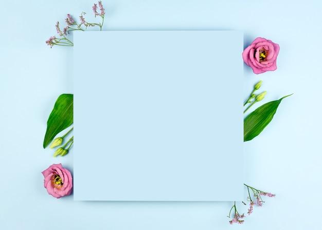 Весенняя композиция. розовые цветы, бумажный бланк на пастельно-синем фоне. плоская планировка, вид сверху, копия пространства, макет.