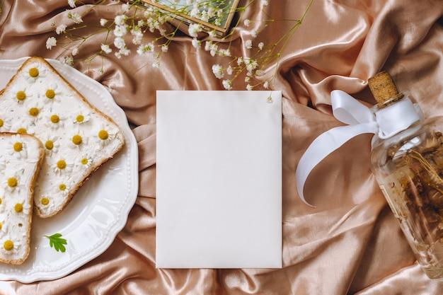 봄 구성, 하얀 빈 종이, 흰 접시에 카모마일 꽃과 토스트 빵 샌드위치