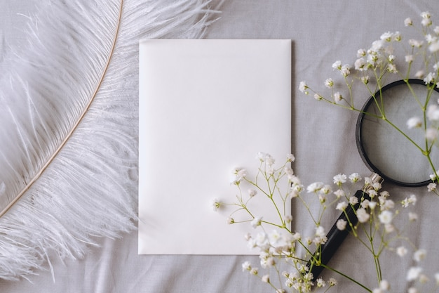 Spring composition, white empty blank paper, gypsophila flowers, magnifying glass and white feather