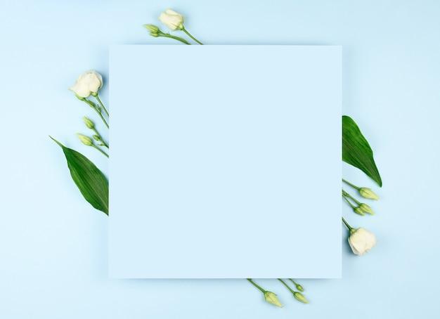 봄 구성. 흰 꽃, 파스텔 블루 배경에 빈 종이.