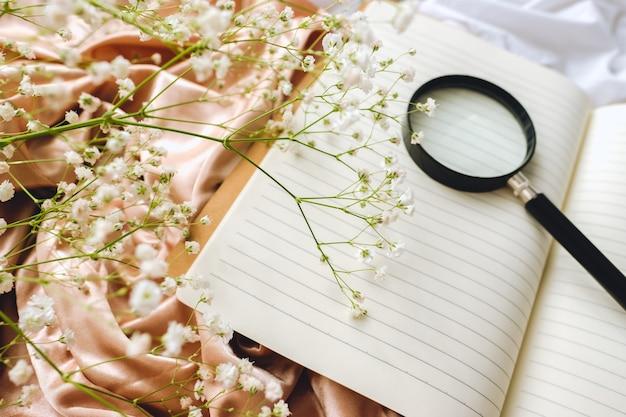 봄 구성, 노트북이 달린 흰색 안개꽃 꽃과 골드 새틴 패브릭에 돋보기