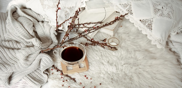 Весенняя композиция с чашкой чая, цветущими ветками и вязанным элементом.