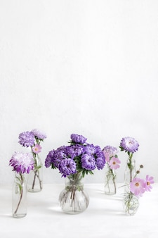 Spring composition with chrysanthemum flowers in glass vases on a blurred white background, copy space.