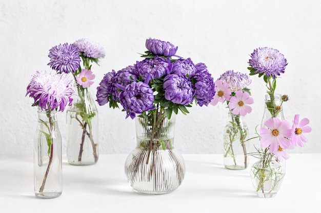 Composizione primaverile con fiori di crisantemo in vasi di vetro su uno sfondo bianco sfocato.