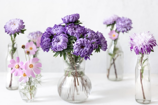 Spring composition with chrysanthemum flowers in glass vases on a blurred white background.