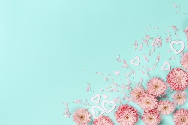 パステルカラーの背景に花、花びら、ハートと春の構成
