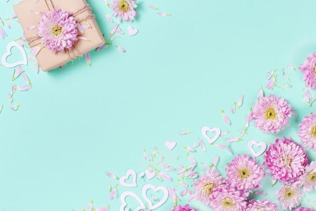 パステルカラーの背景に花、花びら、ハート、ギフトボックスと春の構成