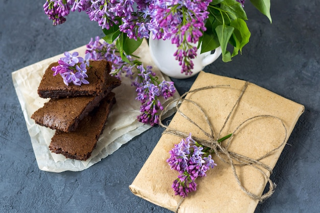 Spring composition with gift box, lilac flowers and brownie, wet cake. dessert for served for tea or coffee break in wooden box. snack on a spring day in the garden.