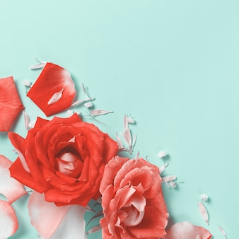 Spring composition with roses, petals, hearts and gift box on a pastel  background