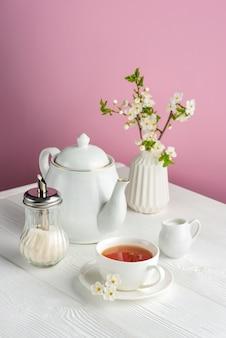 ピンクの背景に白茶道具と春の構成。白いテーブルの上にお茶、ティーポット、ミルクジャグ、桜とカップ。