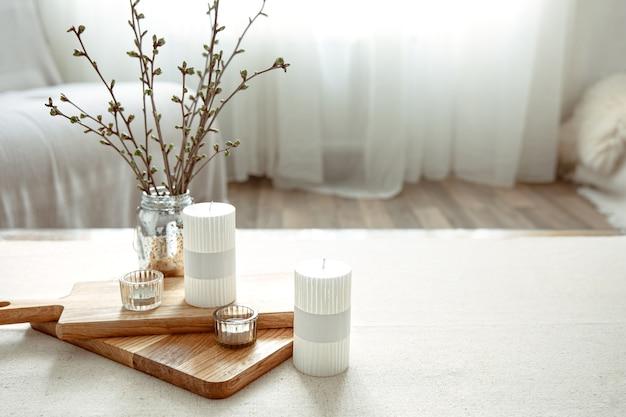 Весенняя композиция с молодыми веточками в вазе со свечами в интерьере комнаты.