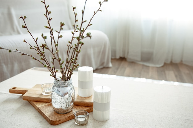 Spring composition with young twigs in a vase with candles in the interior of the room.