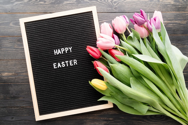Spring concept. bouquet of colorful tulip flowers and letter board with the words happy easter top view flat lay on black wooden background
