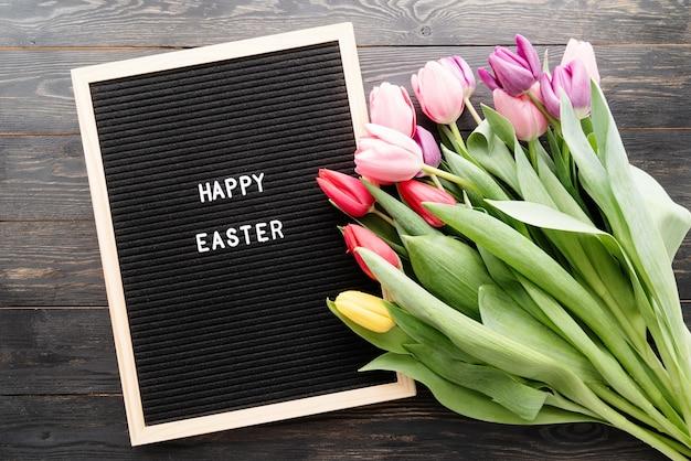 봄 개념. 화려한 튤립 꽃과 편지 보드의 꽃다발 행복 한 부활절 상위 뷰 평면 검은 나무 배경에 누워