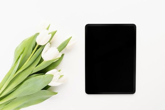 봄 개념. 흰색 튤립 꽃의 꽃다발과 디지털 태블릿 평면도 평면 누워 모의
