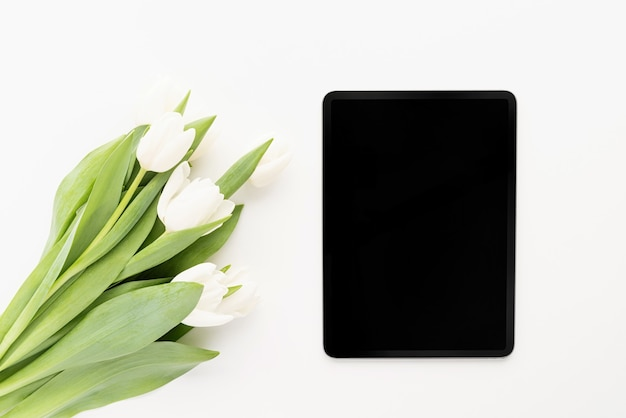 Spring concept. bouquet of white tulip flowers and mock up digital tablet top view flat lay