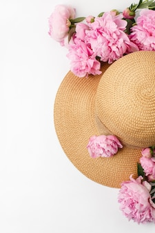 Spring concept, straw braided hat, pink peony flowers on white surface, top view