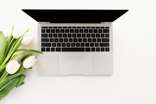 봄 개념. 노트북 컴퓨터, 흰색 튤립 꽃을 모의의 상위 뷰