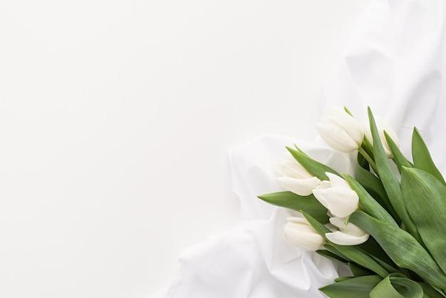 봄 개념. 흰색 튤립 꽃다발과 직물 복사 공간 흰색 배경에 디자인을 모의