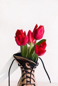 靴と春のコンセプト。花と白い背景の上のベージュの靴。コピースペース