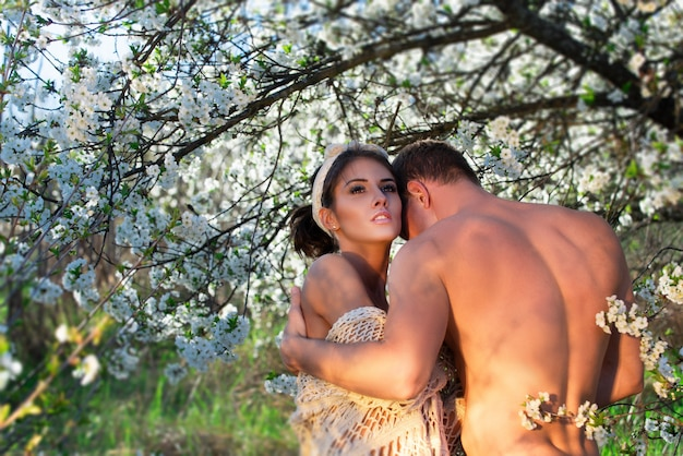 Spring couple in love. summer happiness. sensual lovers in cherry blossom tree.