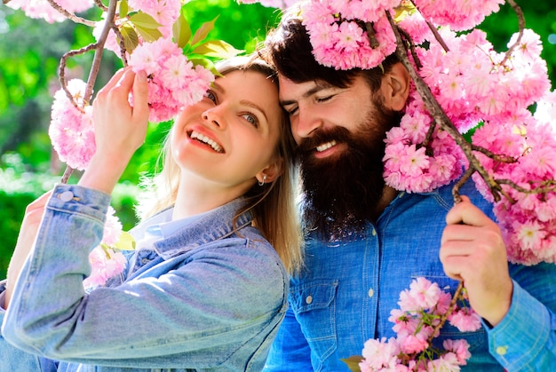 Весенняя пара возле дерева сакуры. счастливая семья в цветущем саду.
