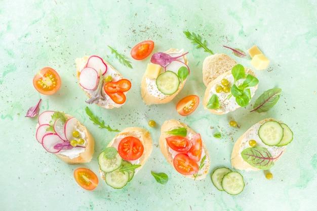 春の食事の健康食品の背景。クリームチーズ、様々な新鮮な野菜とバゲットトーストパンと朝食サンドイッチ。ブルスケッタまたはヘルシーなベジタランベジスナック