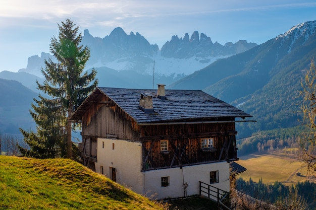 Spring in the dolomites. a view of the houses standing on the green slopes of the mountain. villages san pietro snd santa maddalena.