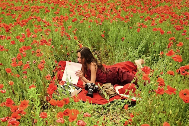 Spring dreams. girl journalism and writing, summer. journalism photographer reporter, writer woman in poppy field.