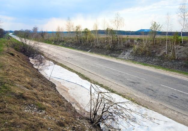 田舎道と雪解けの側にある春の鈍い風景