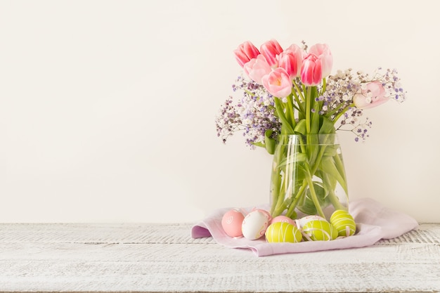 Spring easter composition with bouquet of pink tulips and painted eggs on light background. space for text.