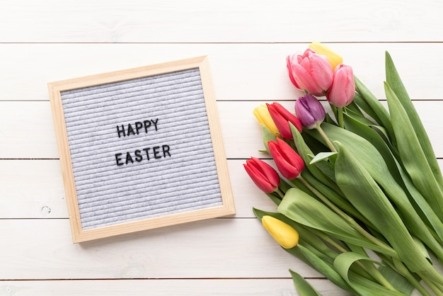 Spring and easter concept. bouquet of colorful tulip flowers and letter board with the words happy easter