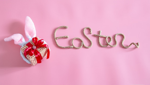 Spring easter festive.easter creative inscription on pink with items of easter decor.