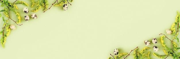 春のイースターの花のボーダー。緑の背景に自然の木の枝、黄色い花とウズラの卵