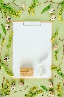 春のイースターの花のフレームと白い白紙。自然の木の枝、黄色い花、ウズラの卵、緑の背景にクリップボードのメモ帳