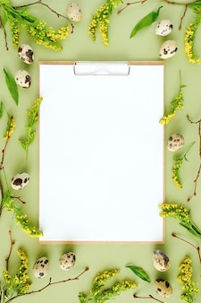 Spring easter floral frame and white blank paper. natural tree branches, yellow flowers, quail eggs, clipboard notepad on green background mockup