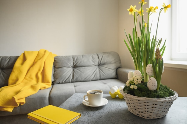Spring easter home interior in living room with cup of coffee, pled and notebook in trendy colors grey and yellow. domestic life.