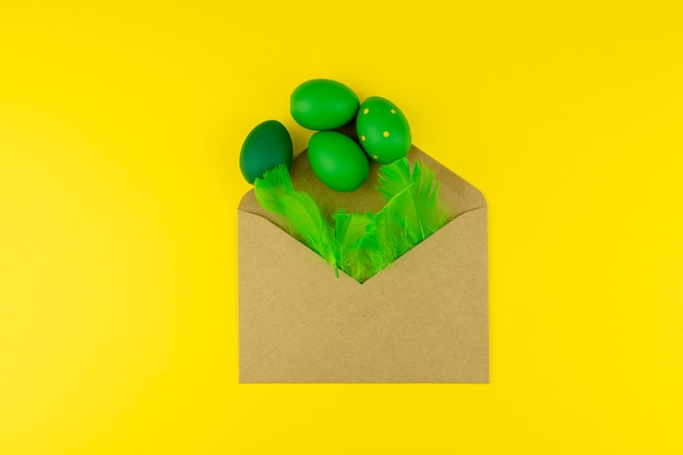 План пасхи весны с зелеными пер и яичками, конвертом корабля на желтой предпосылке. скопируйте место для текста для текста.