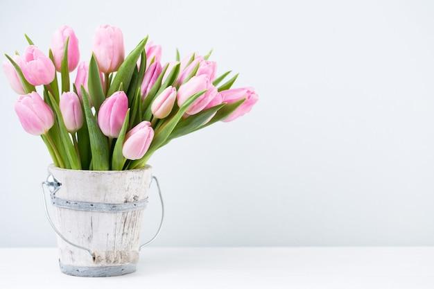 Тюльпаны пасхи весны в ведре на белой винтажной предпосылке.