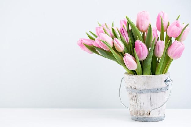 Весенние пасхальные тюльпаны в ведре на белом винтажном