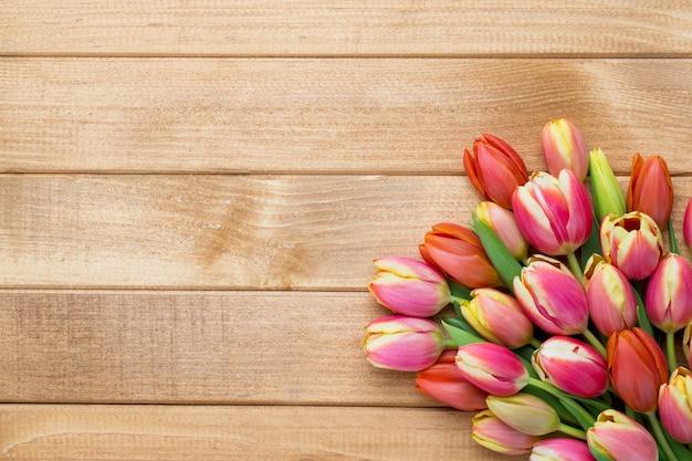 木製のヴィンテージの背景にバケツの春のイースターチューリップ。