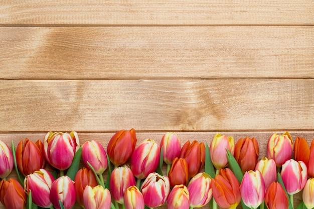 木製のヴィンテージのバケツの春のイースターチューリップ