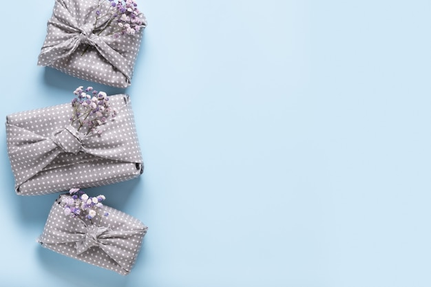 Spring eco-friendly gift wrapped in grey textile with flowers on blue.
