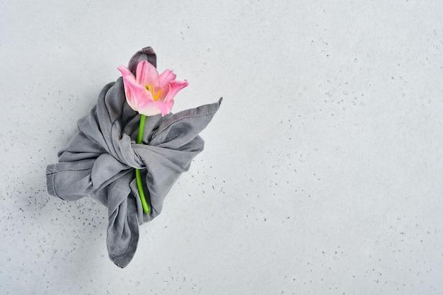 회색 배경에 분홍색 튤립 꽃 장식이 있는 회색 직물로 싸인 봄 친환경 선물