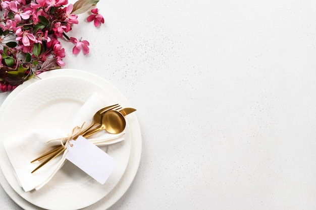 Spring elegance table setting with apple tree flowers, golden cutlery and tag on white table.