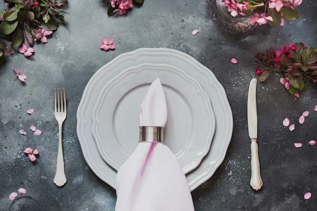 Spring elegant table place setting with romantic pink flowers, silverware on dark background