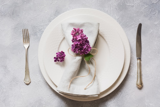 Spring elegant table place setting with violet lilac, silverware on vintage table. view from above.